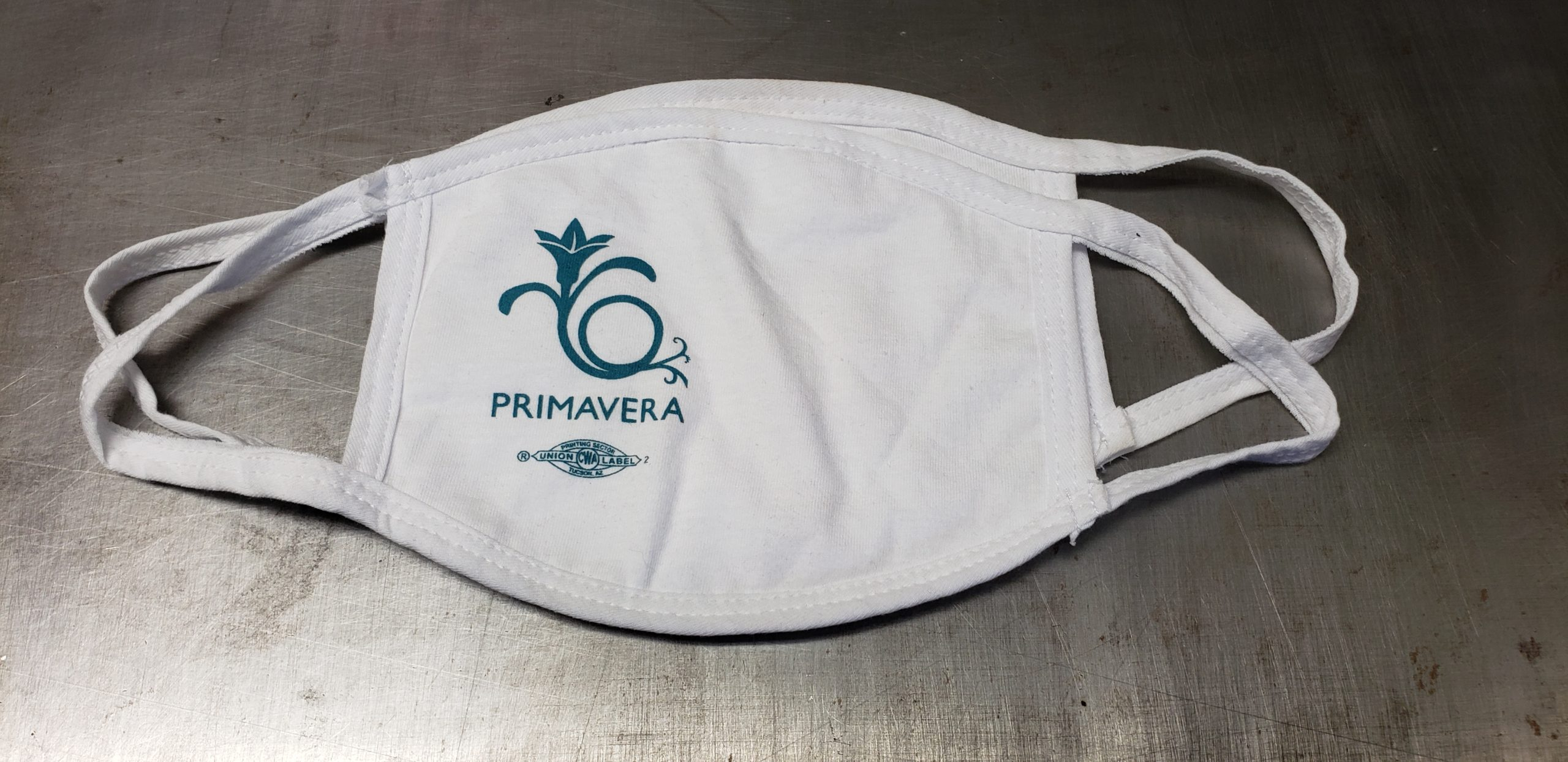White cotton face mask with union screen printed one color logo of the Primavera.