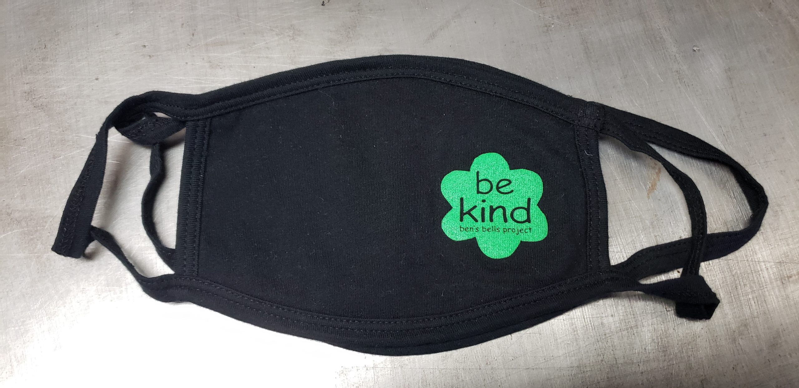 """Black cotton face mask with union screen printed one color design for the ben's bells project that reads, """"be kind"""" in a simple flower shape"""