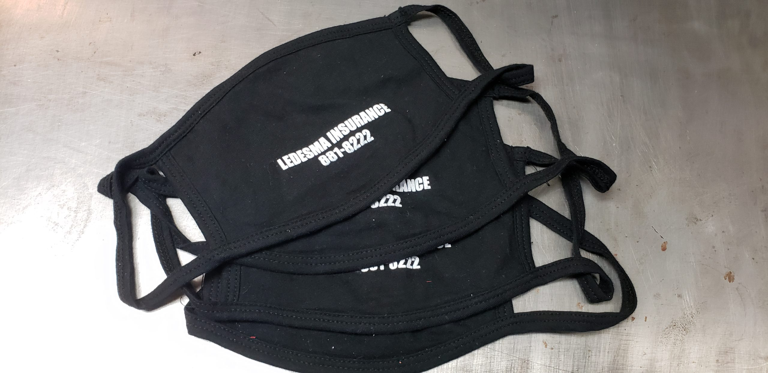 """Several splayed black cotton face mask with union screen printed one color design reading, """"LEDESMA INSURANCE 881-8222"""""""