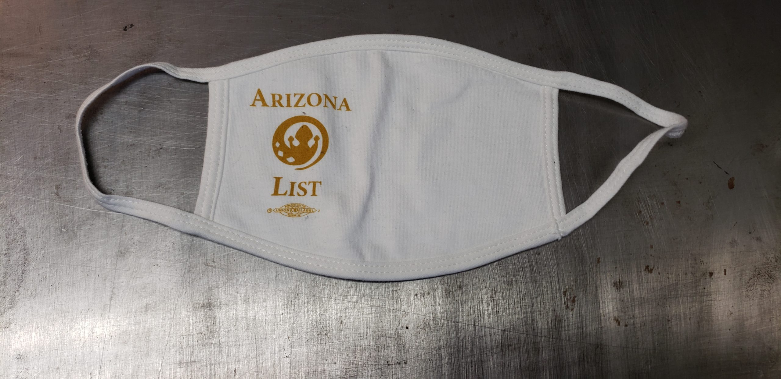 """White cotton face mask with union screen printed one color design reading, """"ARIZONA LIST"""" around a circular spiraling logo of a spade/crown design."""